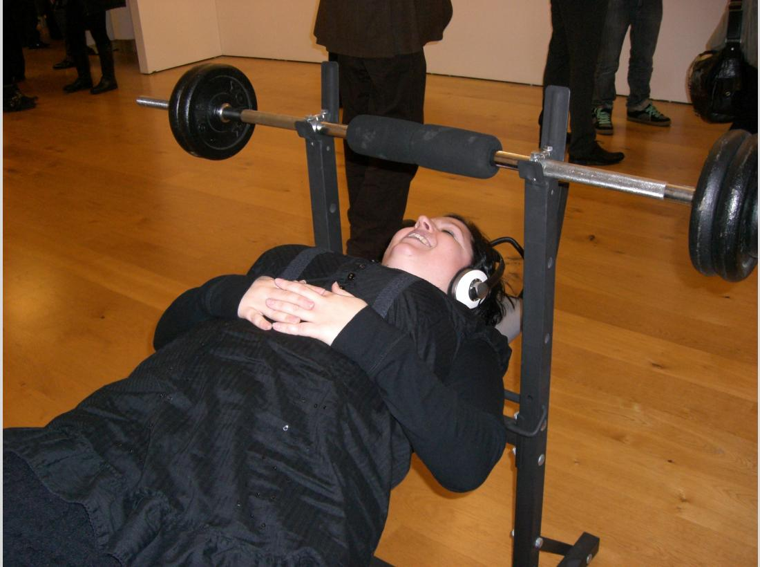 Photograph of someone listening to the First Flight project, headphones attached to a weightlifting bench.