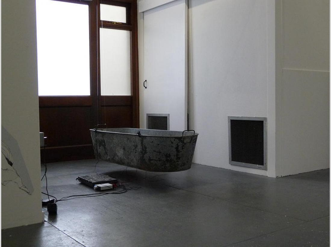 Photograph of resonating tin bath hanging from gallery wall